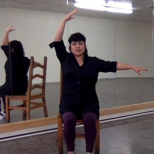 Dance instructor sitting in chair exercising arms