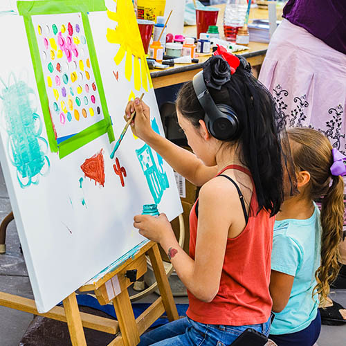 Two children painting on a canvas